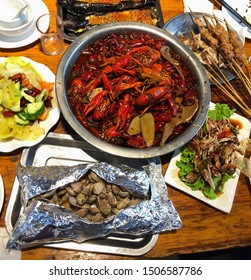 Top view of traditional East China cuisine. Selective focus on spicy boiled crawfish in a a big bowl. Crawfish also kind of freshwater small lobsters. Grilled meat stick. Boiled clams. - Image