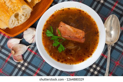 Top view of traditional Russian Shchi - cabbage soup with pork cooked on mushroom broth