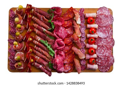 Top view of traditional Spanish meat platter - sliced dry-cured jamon, bacon and sausages on wooden board with olives, tomatoes and greens. Isolated over white background