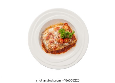 Top view of Traditional style Italian cuisine beef lasagna garnished with parmesan cheese, parsley, and tomatoes in ceramic dish isolated on white background