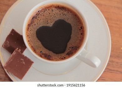 Top view of Traditional Turkish Coffee in a white coffee cup with two piece of chocolate. Heart shape coffee foam. Turkish coffee with foam and bubbles in a shape of a heart.