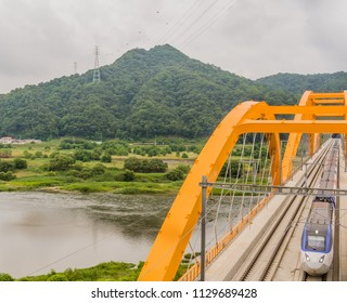 Top view of train crossing yellow arch bridge over a river in countryside under cloudy overcast sky.