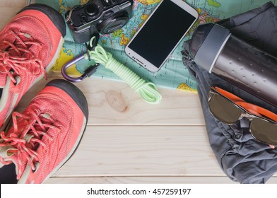 Top view of travel accessories for a mountain trip on old wooden background : hiking boots, pants, camera, bottle, rope, map, smartphone, and sunglasses.