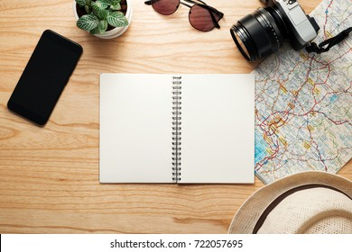 Top view of travel accessories,Traveler concept background,Blank notebook and camera on wooden table.