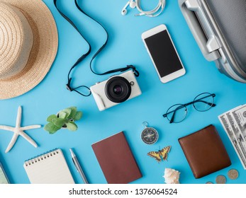 top view travel concept with digital camera, smartphone, map, passport, compass and Outfit of traveler on blue background, Tourist essentials, vintage tone effect