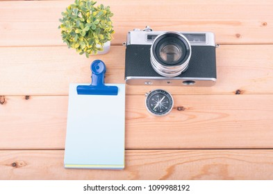 top view travel concept with retro camera films, compass, plant and notepad on wooden background