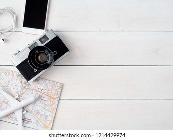 top view travel concept with retro camera films, map, passport, smartphone on white table background with copy space, Tourist essentials, vintage tone effect