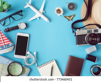 top view travel concept with retro camera films, smartphone, map, passport, compass and Outfit of traveler on blue background with copy space, Tourist essentials, vintage tone effect