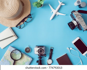 top view travel concept with retro camera films, map, passport, smartphone, action camera and compass on blue background with copy space, Tourist essentials, vintage tone effect