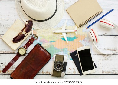 Top view and travel equipment put on wooden floor, camera, passport, airplane model, clock, bell, world map, hat