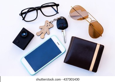 Top view of travel set: camera, car keys,walet,sunglasses,and smartphone on white background