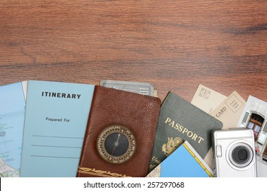 Top view of a travel still life. Items include: passport, wallet, post cards, camera, pictures, maps, and itinerary folder on a wood desk. Horizontal format with copy space at the top.