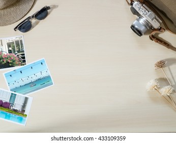 Top view of Travel and vacation photo frames and items, camera, sunglasses, notebook on wooden table on the wooden background ( Composition and space for text )