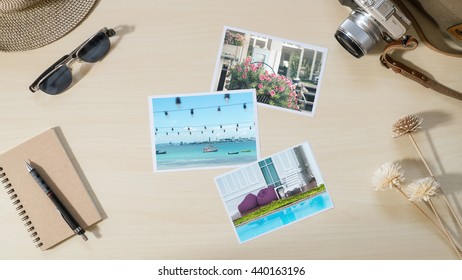 Top view of Travel and vacation photo frames and items, camera, sunglasses, notebook on the wooden background