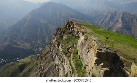 Vue de dessus de voyageurs sur une falaise rocheuse sur fond de hautes montagnes. Action. Vue imprenable de la falaise à la vallée de la montagne avec voile. Hautes montagnes verdoyantes avec un brouillard clair les jours ensoleillés