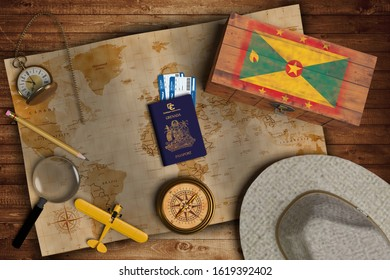 Top view of traveling gadgets, vintage map, magnify glass, hat and airplane model on the wood table background. On center, official passport of Grenada and your flag.