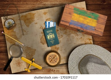 Top view of traveling gadgets, vintage map, magnify glass, hat and airplane model on the wood table background. On center, official passport of Gabon and your flag.