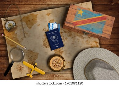Top view of traveling gadgets, vintage map, magnify glass, hat and airplane model on the wood table background. On center, official passport of Republic of the Congo and your flag.
