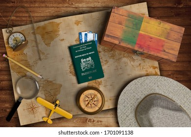 Top view of traveling gadgets, vintage map, magnify glass, hat and airplane model on the wood table background. On center, official passport of Benin and your flag.