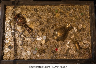 Top view of treasure chest full of gold coins, gold vase and pot