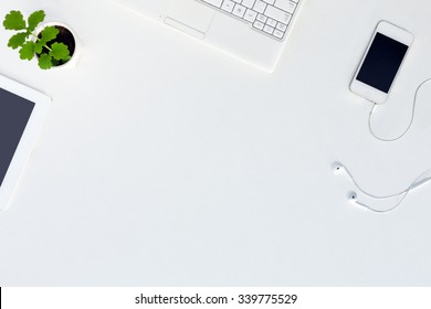 Top View of trendy White Office Desk with white Cropped Laptop Tablet Telephone Earphones Electronics and green Flower