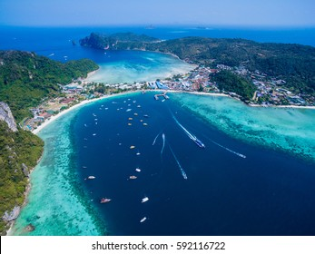 Top view of tropical island with limestone rocks and blue clear water. Aerial view of Tonsai bay with many boats and speedboats above coral reef. Phi-Phi Don Island, Thailand.