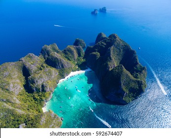 Top view of tropical island with limestone rocks, white beach and blue clear water. Aerial view of Maya bay with many boats and speedboats above coral reef. Phi-Phi Islands, Krabi, Thailand.