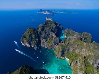 Top view of tropical island with limestone rocks and blue clear water. Aerial view of snorkeling people near speedboats above coral reef. Phi-Phi Islands, Thailand.