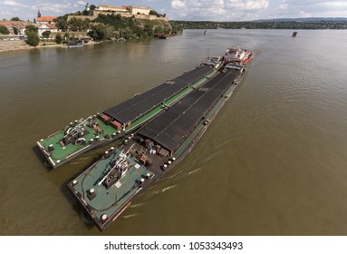 Top view of Tugboat pushing a heavy barge on the river