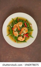 Top view of Tumis Udang Daun Bawang or Stir fry Leek Prawns with chili and oyster sauce as Asian food. Served on white plate with bamboo coaster in dark grainy background. Selective focus