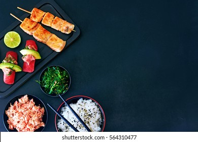 Top view of tuna sushi, grilled salmon on skewers, bowl or rice, crab meat and wakame salad over dark board with a copy space. Gourmet japanese dinner.
