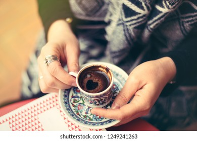 Top view to turkish coffee in tradition coffee cup with ornaments in woman's hands. Heart shape
