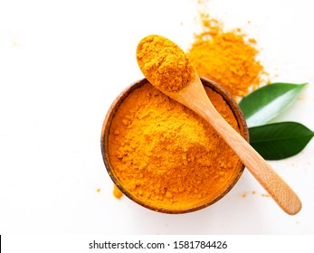 Top view of turmeric powder in spoon and wooden bowl with green leaves isolated on white background.