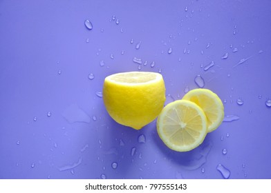 Top view of turn up half piece of fresh lemon with water splash on blue background with copy space