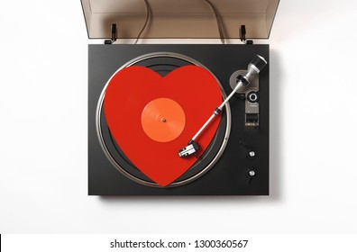 Top view of a turntable with a rotate red heart-shaped vinyl record a stylus with a needle, on a white background. Valentine's Day. Love