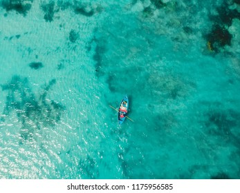Top view of turquoise ocean water and fisherman on boat, aerial drone shot