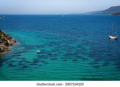 Top view of the turquoise water bay near corsican Porticcio town with boats in the wetr and mountains on the background.