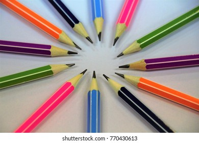 Top view of twelve drawing pencils on white background. Group of pencils many colors.