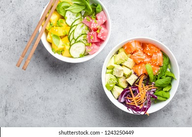 Top view of two assorted poke bowls with fresh raw tuna, salmon, vegetables, fruit. Traditional Hawaiian dish on rustic stone background. Healthy and clean eating concept. Poke with slices of raw fish
