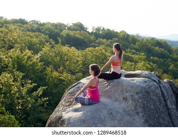 Top view of two athletic barefooted women sitting in lotus pose on top of huge rocks on green mountains and clear blue sky background. Yoga, fitness and healthy lifestyle concept. Siddhasana