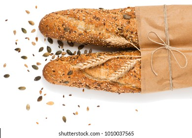 Top view of two baguettes baked bread in paper with different seeds ( pumpkin, poppy, flax, sunflower, sesame, millet ) decorated with ears of wheat isolated on white background.