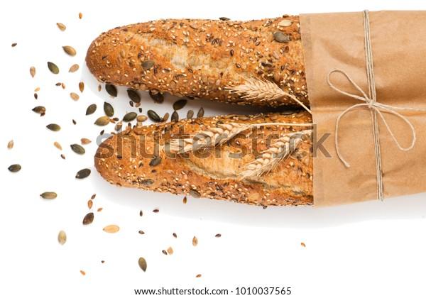 Вид сверху из двух багетов, запеченных хлебом в бумаге с различными семенами (тыква, мак, лен, подсолнечник, кунжут, просо) украшены колосьями пшеницы, выделенными на белом фоне.