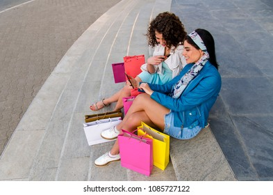 Top view two beautiful girls with shopping bags sitting on stairs and looking at smart phone