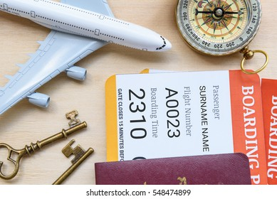 Top view of two boarding pass with passports on a wood floor, decorated with a compass, a white model airplane, brass keys. Concepts about aviation, travel or transportation by air, vacation trip, etc
