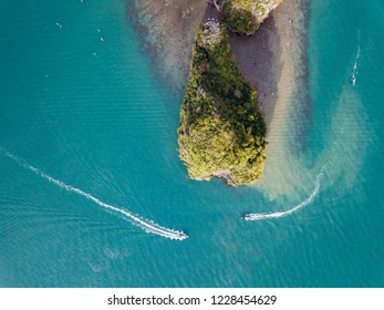 Top view of two boats go around a rocky island in a tropical sea, Thailand