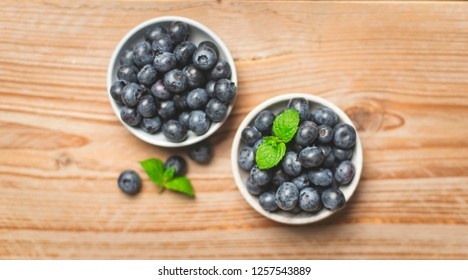 Top view of two bowls of bluberries on wooden table with fresh mint leaves