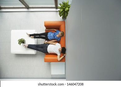 Top view of two casual people reclining on couch in reception room at office