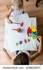 Top view of two children painting with watercolors with brush and a colorful palette on small white table.