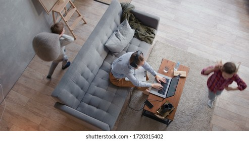 Top view two children run around stressed young mother trying to work from home on laptop. Family life on lockdown.