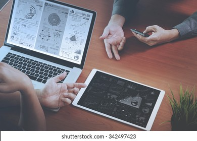 top view of two colleagues discussing data with new modern computer laptop and pro digital tablet with digital business strategy layer effect on wooden desk as concept
